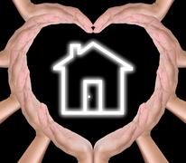 House icon in hands created heart Stock Photos