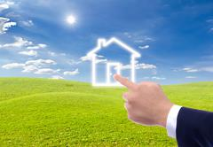 hand pointing to house icon - stock photo