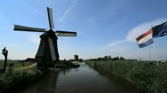Netherlands Kinderdijk windmill turning reflected in canal 6 Stock Footage
