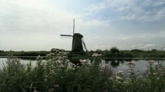 Netherlands Kinderdijk windmill behind flowers and still water 1 Stock Footage
