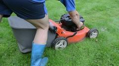 Gardener worker shorts rubber boots start grass lawn mower push Stock Footage