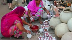 Women paint pots in the city market - Jodhpur India Stock Footage