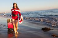 An attractive woman in Santa Claus costume pulling a sleigh Stock Photos