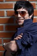 Stock Photo of man near brick wall