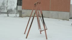 Empty swing seat move winter snowstorm wizzard snow fall Stock Footage