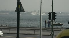 People walking, with traffic in foreground, Bosporus straits in bg Stock Footage