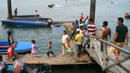 People getting on boat from boardwalk Stock Footage