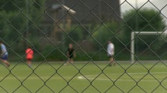 Players on Soccer field behind fence Stock Footage