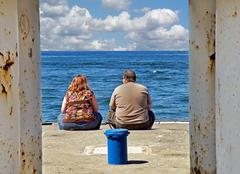 obese couple sitting on pier - stock photo