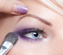makeup artist applying eyeshadow - stock photo