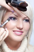 Makeup artist applying eyeshadow Stock Photos