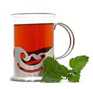 tea in a glass holder and a sprig of lemon balm - stock photo