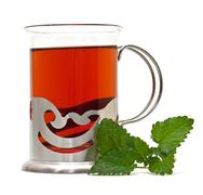 Stock Photo of tea in a glass holder and a sprig of lemon balm