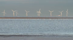 Windturbines with ferry passing in the irish sea off, wirral, england Stock Footage