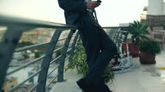 Angry businessman talking on cellphone on the terrace, crane shot Stock Footage