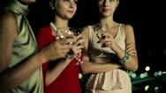 Three female friends enjoying night party on the terrace, crane shot Stock Footage