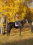 Kaunis nainen ja musta hevonen Kuvituskuvat