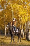 Beautiful woman and a dark horse Stock Photos