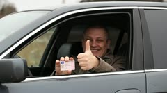 Happy man with a driver's license in hand Stock Footage