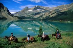 4 horse riders with Mountain Lake Stock Photos