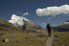 back packer on snow capped mountain trail - stock photo