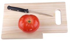 wood kitchen board with knife and tomato - stock photo