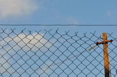 chain link fence and blue sky - stock photo