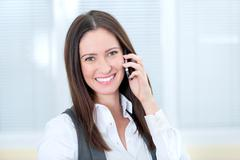 smiling business lady with mobile phone - stock photo