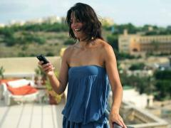 Happy woman taking foto with cellphone on the terrace - stock footage
