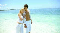 Couple walking hand in hand on a paradisiacal beach Stock Footage