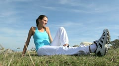Woman in fitness outfit relaxing outside in countryside Stock Footage
