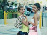 Happy young female friends walking with shopping bags in the city, slow motion Stock Footage