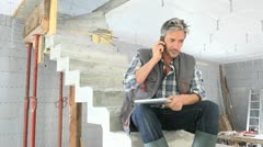construction manager using mobile phone on building site - stock footage