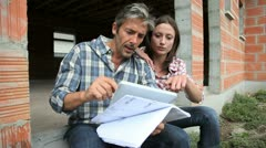 couple sitting in house under construction - stock footage