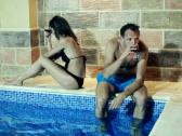Relationship difficulties: couple after quarrel by the swimming pool at night Stock Footage