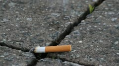 Cigarette on pavement - stock footage