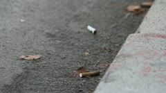 Cigarettes in gutter - stock footage