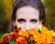 a beautiful brunette with flowers - stock photo