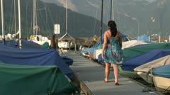 Female walking down boat dock Stock Footage
