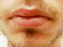closup of dry male lips, surrounded with beard - stock photo