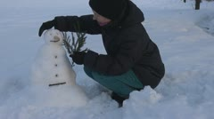 Young woman arrange her snowman, winter girl countryland holidays snow happy - stock footage