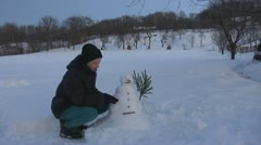 Young woman arrange her snowman, winter snow play fun girl holiday park nature - stock footage