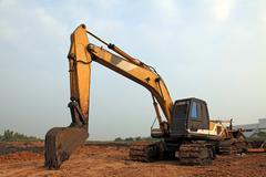 excavator loader with backhoe standing in sandpit - stock photo