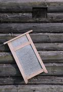washboard on old log house wall - stock photo