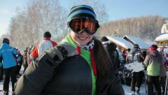 Stock Video Footage of A girl in snowboard clothes comes to the camera and smiles happily.