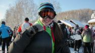 A girl in snowboard clothes comes to the camera and smiles happily. Stock Footage