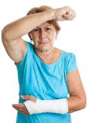 Elderly woman with a broken arm defending herself against an agg Stock Photos