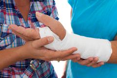 woman with a broken arm and her caregiver - stock photo