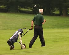 GOLF player carrying golf bag Stock Footage