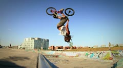 BMX Bicycle Back Flip Slow Motion in Graffiti Covered Skateboard Park Stock Footage
